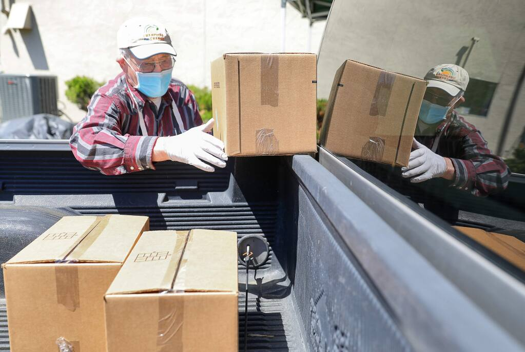 Redwood Empire Food Bank volunteer Al Lenhardt loads boxes of food into a client's truck during a food distribution event at Shiloh Neighborhood Church, in Santa Rosa on Wednesday, April 15, 2020. (Christopher Chung/ The Press Democrat)