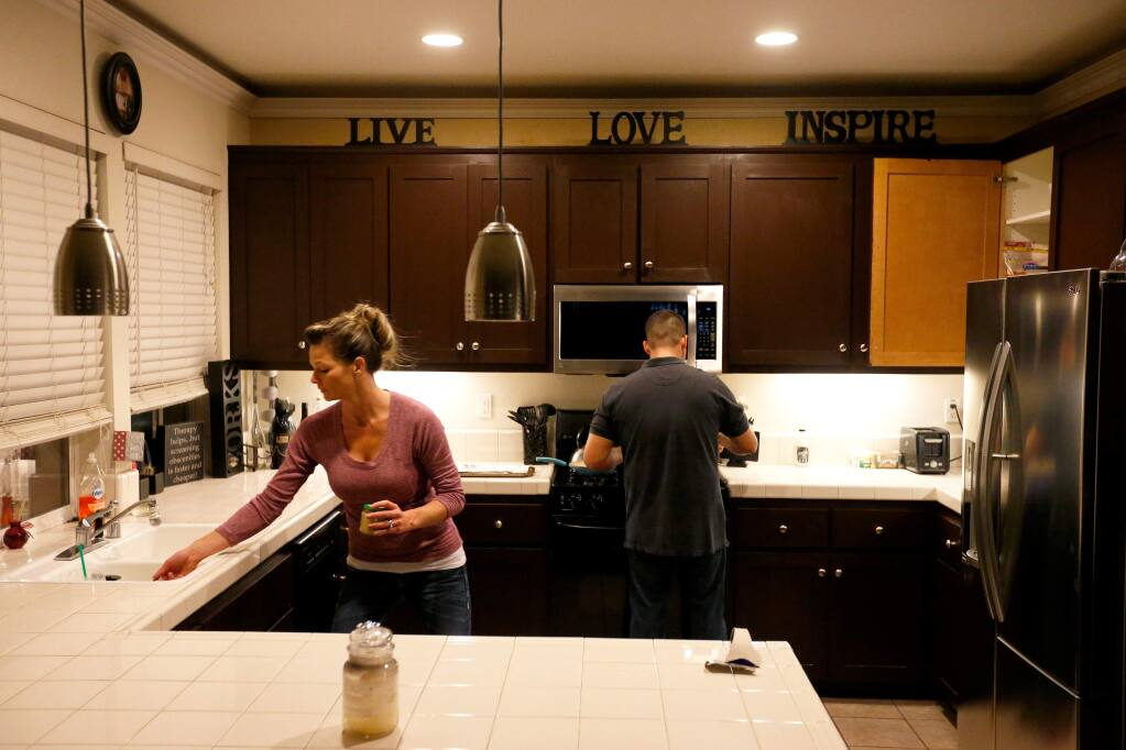 Jill and Manny Castrellon get started preparing dinner at their home, in Santa Rosa, California on Wednesday, January 6, 2016. (Alvin Jornada / The Press Democrat)