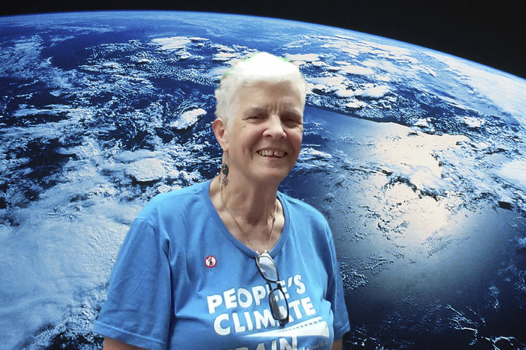 TISH LEVEE Flanked by the love of her life, Mother Earth. (Photo from Jewish groups 2014 climate march. - Courtesy Tish Levee)