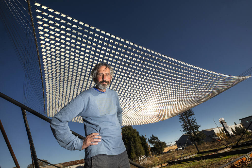 """World-renowned artist Ned Kahn stands below his """"Wind Hammock"""" with thousands of pivoting metal squares that move with the wind in a temporary """"Air Garden"""" on the site of the future Hotel Sebastopol on Friday, Dec. 11, 2020. (John Burgess / The Press Democrat)"""