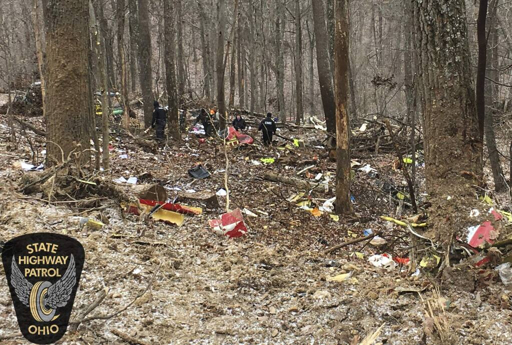 In this photo provided by the Ohio State Highway Patrol, authorities survey the scene of wreckage where a medical helicopter crashed in a remote wooded area in Brown Township, Ohio, on its way to pick up a patient, Tuesday, Jan. 29, 2019. (Ohio State Highway Patrol via AP)