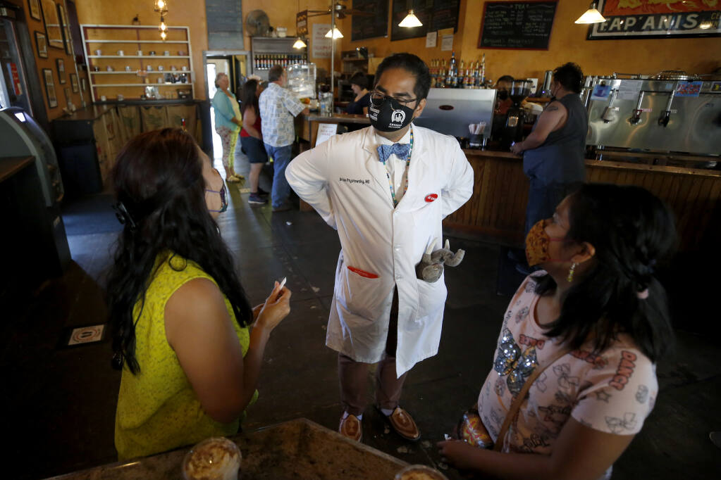 Dr. Brian Prystowsky talks with Irma Garcia and her daughter Francis Escobedo, 9, at A'Roma Roasters Coffee & Tea as he tries to spread the word about free Covid-19 vaccines available Sunday at the Arlene Francis Center in Santa Rosa, Calif., on Sunday, June 27, 2021.(Beth Schlanker/The Press Democrat)