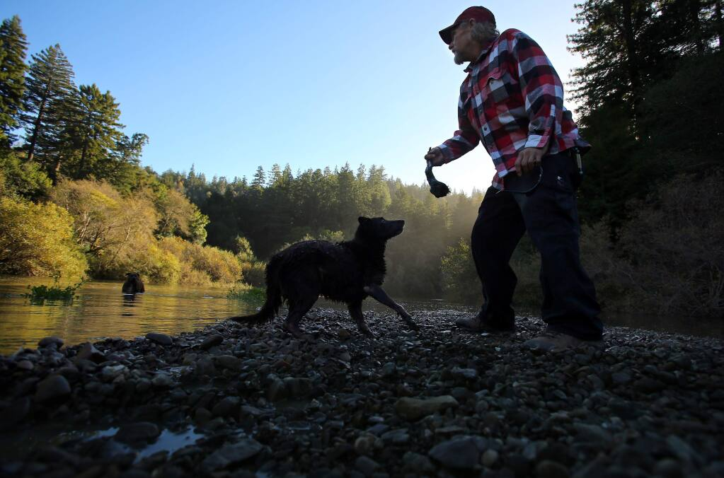 Gary Lukas, of Point Arena, tosses a stick for his dog, Jake, at the Gualala River, along Gualala River Road, on Monday, November 24, 2014.(Christopher Chung/ The Press Democrat)