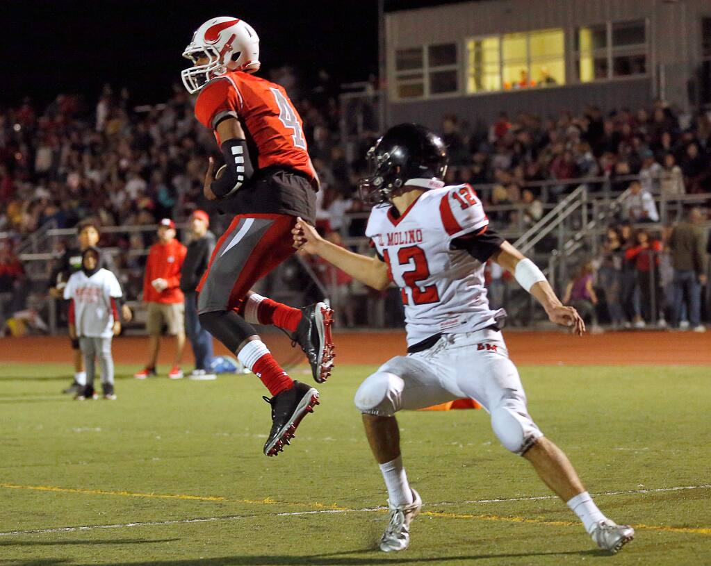Montgomery's Kaih Johnson, left, turns and leaps to catch a touchdown pass while covered by El Molino's Wyatt Stringfellow during the first half between El Molino and Montgomery high schools, in Santa Rosa on Friday, Oct. 19, 2018. (Alvin Jornada / The Press Democrat)