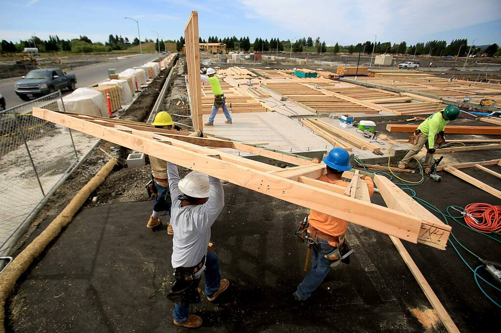 Workers with Richmond American put up framing of a new home in a large housing project near Sonoma State University in Rohnert Park on Friday, June 10, 2016. (KENT PORTER/ PD)