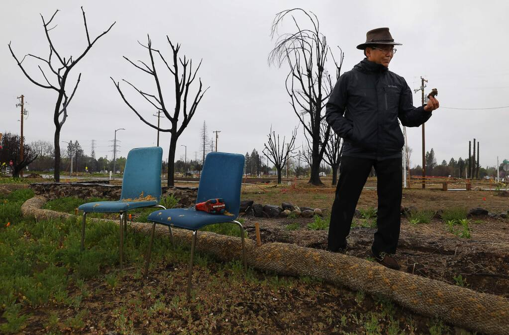 Dr. Marshall Kubota picks up a piece of sponge in the backyard area of his burned home along Pacific Heights Drive in Santa Rosa on Thursday, April 5, 2018. (CHRISTOPHER CHUNG/ PD)