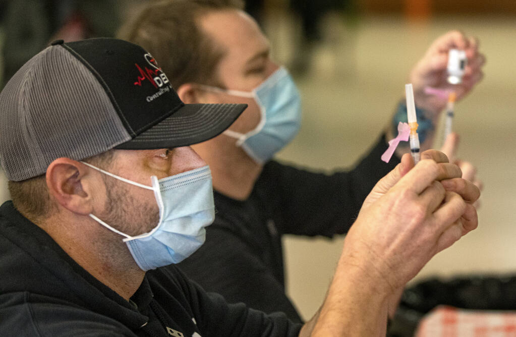 Paramedic Brandon Bruce, left, and RN Tim Adams fill syringes with doses of the Moderna COVID-19 vaccine for Phase 1 health care and care facility workers at the Roseland Regional Library vaccination site on Thursday, Jan. 22, 2021. (John Burgess / The Press Democrat)