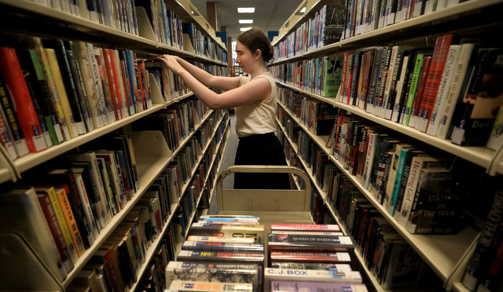 Logan Manchester refiles returned books at the main branch of the Sonoma County Library, Tuesday, June 25, 2019 in Santa Rosa. (Kent Porter / The Press Democrat)