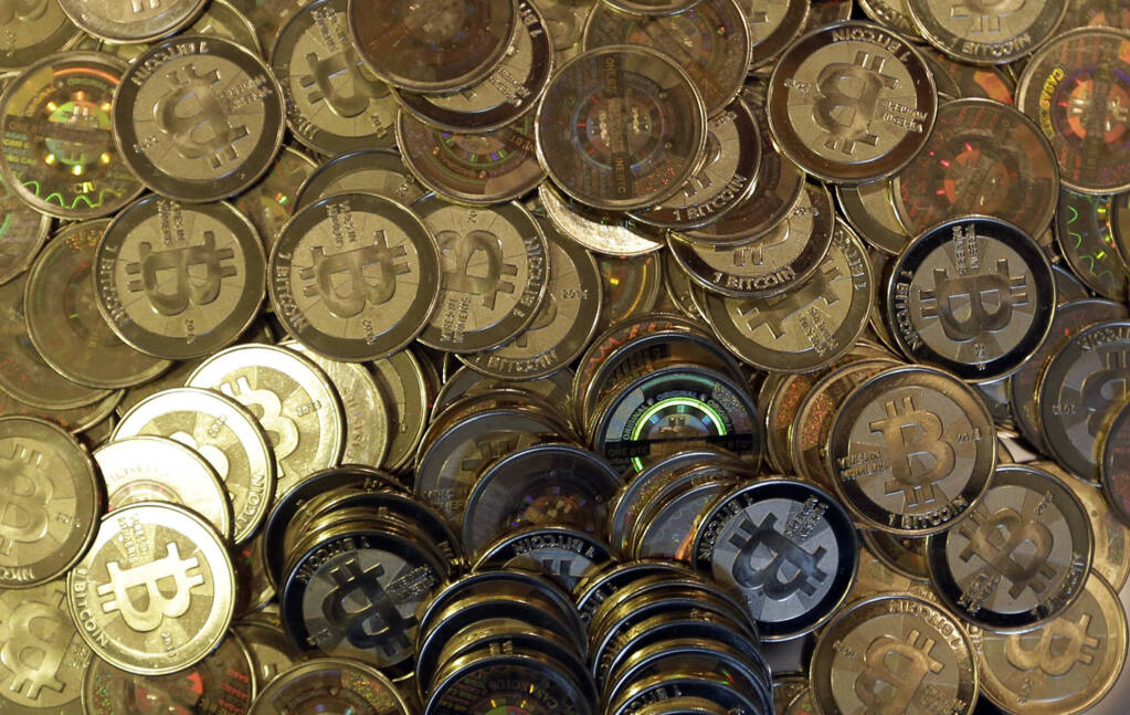 FILE - This April 3, 2013 file photo shows bitcoin tokens in Sandy, Utah. Bitcoin, a virtual currency that sometimes takes the form of tokens, has broken through in Sonoma County with a store accepting it as payment. (AP Photo/Rick Bowmer, File)