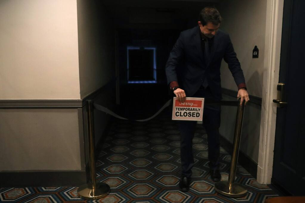 Hotel Petaluma general manager Dustin Groff adjusts a closed sign on a floor of the hotel that was temporarily closed on March 18, 2020, to save resources and money during the coronavirus pandemic. (BETH SCHLANKER/The Press Democrat)
