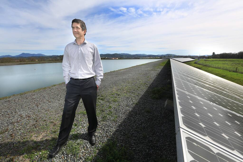 Sonoma County Water Agency Deputy Chief Engineer Cordel Stillman stands next to solar panels on a levee at a water treatment holding pond. (Kent Porter / PD File Photo, 2015)