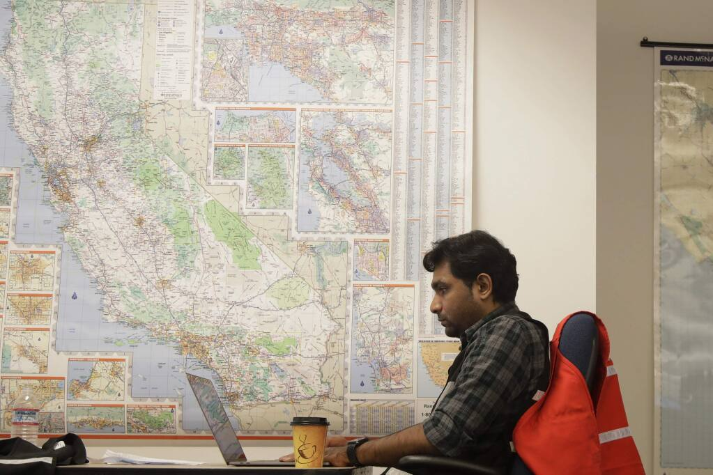 FILE - In this Oct. 10, 2019, file photo, Senior program analyst Siva Jasti works next to a map of California in the Pacific Gas & Electric (PG&E) Emergency Operations Center in San Francisco. The California Senate will investigate a California utility's process for cutting off power to more than 2 million people to prevent wildfires. In a memo to the Senate Democratic Caucus on Thursday, Oct. 17, 2019, Senate President Pro Tempore Toni Atkins asked the Senate Energy, Utilities, and Communications Committee to 'begin investigating and reviewing options to address the serious deficiencies' with PG&E's current process of shutting off power to prevent wildfires. (AP Photo/Jeff Chiu, File)