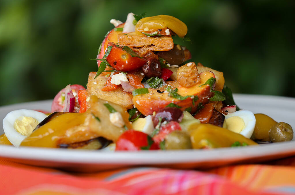 Israeli Salad, with tomato, peach, red pepper, radish, cucumber, feta cheese, egg, sauteed eggplant and a spiced mango puree, prepared by Matt Spector at Zoftig Eatery. (Christopher Chung/ The Press Democrat)