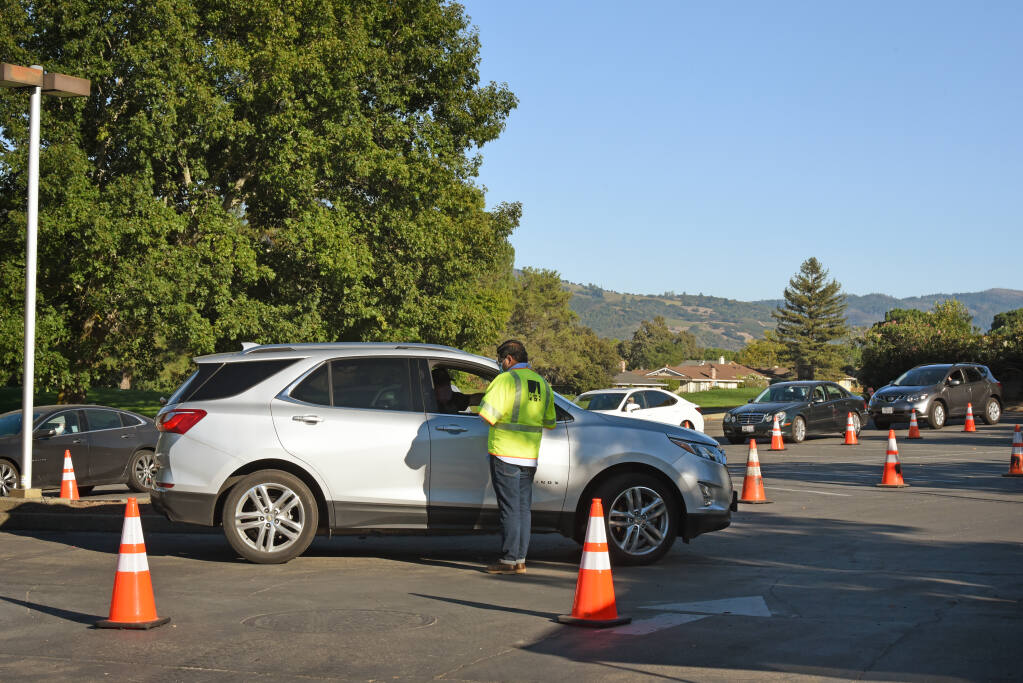 PG&E setup a check-in to help coordinate gas restoration for residents in the parking lot of the Valley of the Moon Club after mandatory evacuation orders were lifted in Oakmont Village of Santa Rosa, Calif. on Sunday, October 4, 2020.(Photo: Erik Castro/for The Press Democrat)