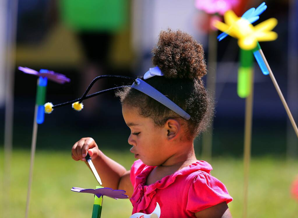 Esme Iddeen, 4, of Petaluma pretends she's a bee polinating flowers in a game sponsored by the Sonoma County Beekeepers Association at the Farmer Olympics at the Petaluma Fairgrounds on Saturday. (John Burgess/The Press Democrat)