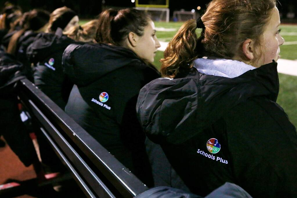 Santa Rosa's Katie Jo Brumbaugh, right, and Lucy Matthiessen and their Panthers teammates keep warm by wearing their new winter coats during a girls varsity soccer game between Santa Rosa and El Molino high schools in Forestville, California, on Friday, January 17, 2020. The team's winter coats were funded by a donation and grant through the nonprofit organization Schools Plus. (Alvin Jornada / The Press Democrat)