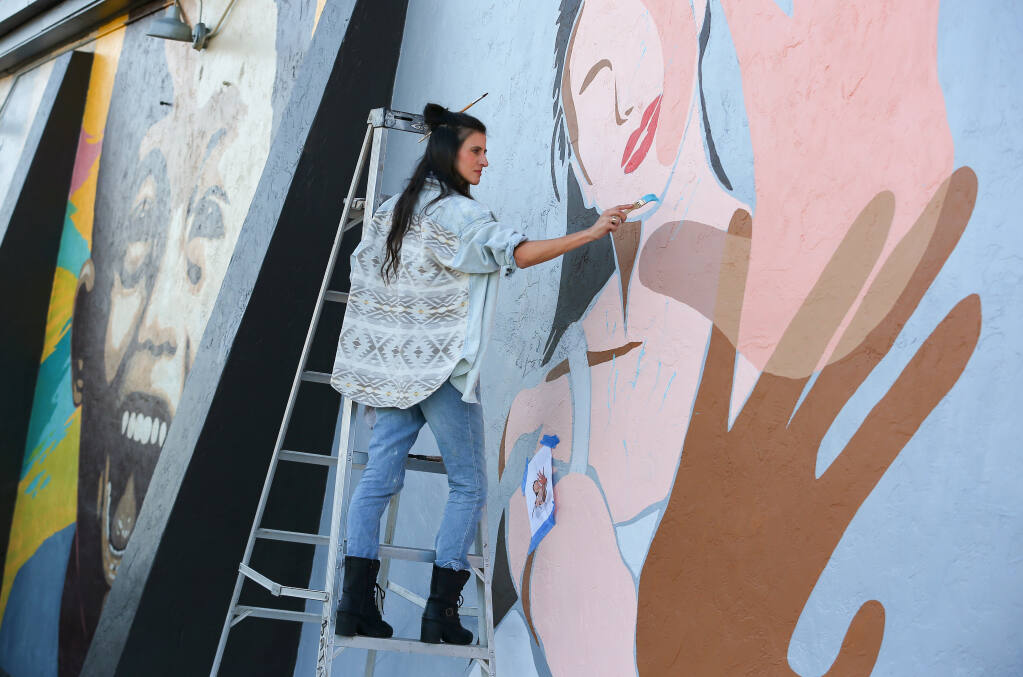 Artist Rachel Brooks works on a mural on the side of the Fulton Crossing Gallery building in Fulton on Thursday, October 29, 2020.  (Christopher Chung/ The Press Democrat)