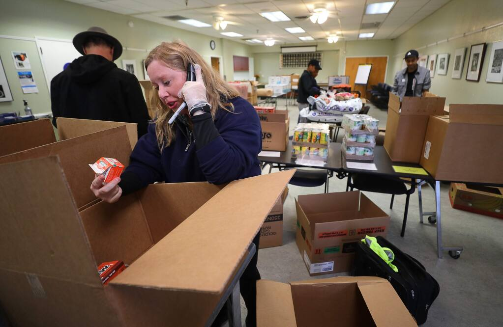 Anna Grant, active adult and senior services supervisor with the City of Healdsburg, talks with a senior citizen on the phone to determine what food they want delivered to their home, at the Healdsburg Senior Center on Wednesday, March 18, 2020. The Redwood Empire Food Bank provided the food for delivery to seniors.(Christopher Chung/ The Press Democrat)
