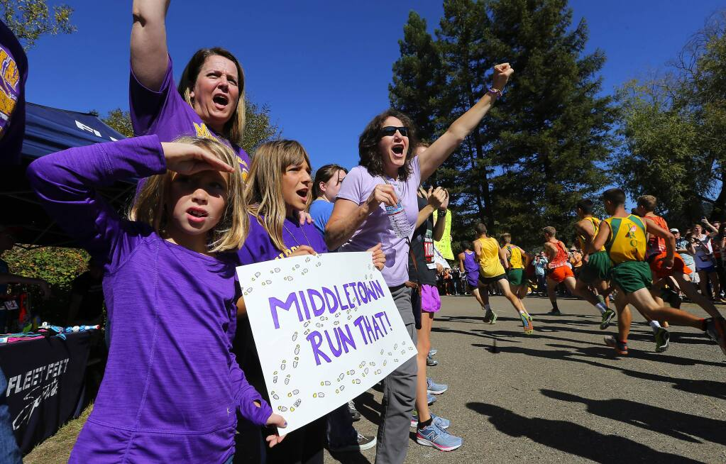 Middletown cross country supporters Maggie Rae Olson, Brooke Robles and Marcella Robles cheer on their team on the Spring Lake course in Santa Rosa on Saturday. (JOHN BURGESS / The Press Democrat)