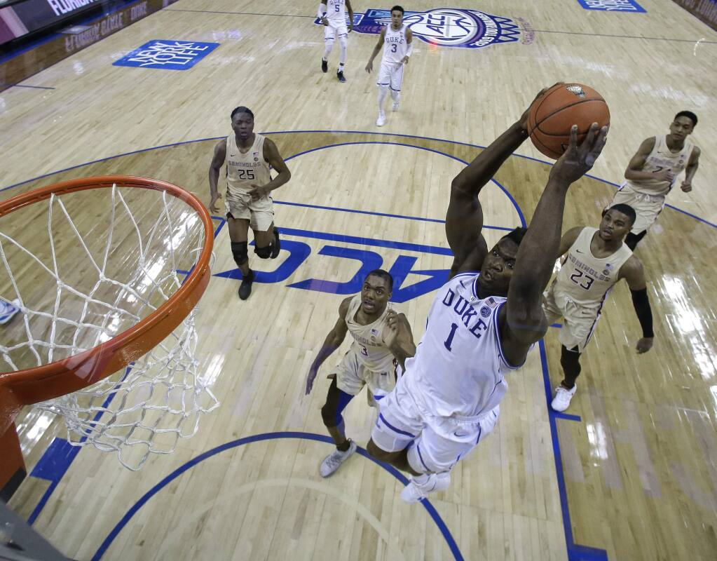 Duke's Zion Williamson goes up to dunk against Florida State during the first half of the championship game of the Atlantic Coast Conference tournament in Charlotte, N.C., Saturday, March 16, 2019. (AP Photo/Chuck Burton)