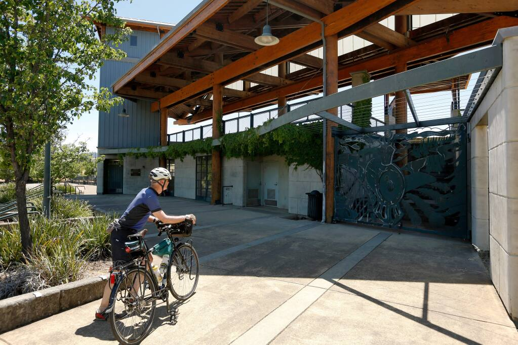 Dwayne Price of Larkspur dismounts his bicycle for a closer look at the Cloverdale Train Station in Cloverdale, California, on Friday, June 8, 2018. Price and his wife rode the SMART train from San Rafael to Santa Rosa for a northbound weekend bike excursion. (Alvin Jornada / The Press Democrat)