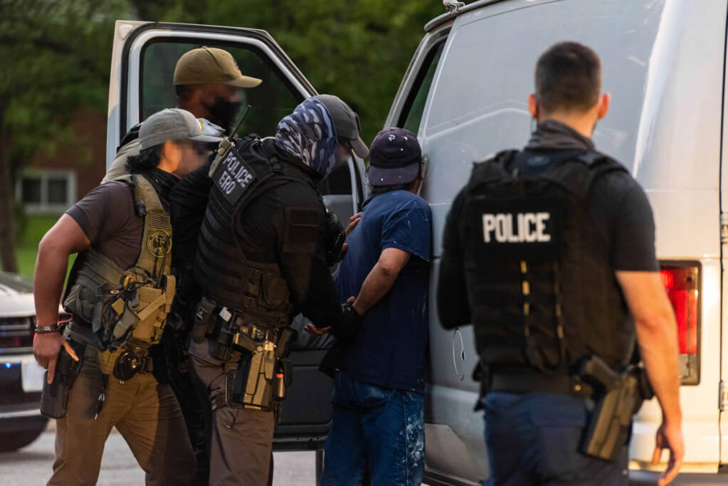Immigration and Customs Enforcement officers detain a man on a recent Enforcement and Removal Operation; location and identification unavailable.
