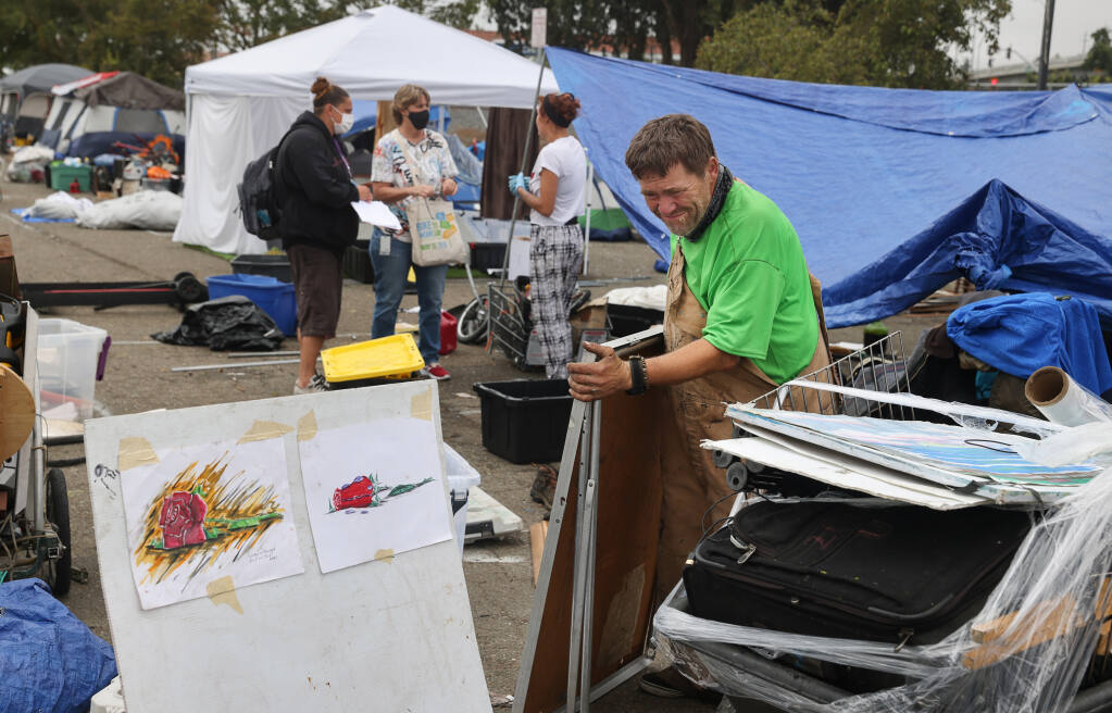 Richard Wayne Seward packs up his belongings from the homeless encampment at the Roberts Lake Park and Ride lot in Rohnert Park on Friday, September 10, 2021.  (Christopher Chung/ The Press Democrat)