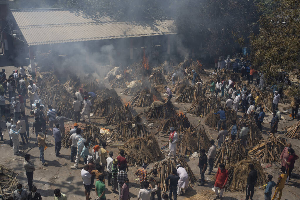 FILE - In this April 24, 2021, file photo, multiple funeral pyres of those who died of COVID-19 burn at a ground that has been converted into a crematorium for the mass cremation of coronavirus victims, in New Delhi, India. India's excess deaths during the pandemic could be a staggering 10 times the official COVID-19 toll, likely making it modern India's worst human tragedy, according to the most comprehensive research yet on the ravages of the virus in the south Asian country. (AP Photo/Altaf Qadri, File)
