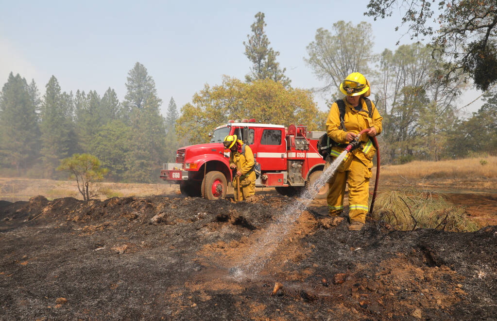 Hopland Fire District firefighters Daisy Smith, right, and Albert Farrens put out hotspots along Friesen Road near  Angwin on Tuesday, September 29, 2020.  (Christopher Chung/ The Press Democrat)