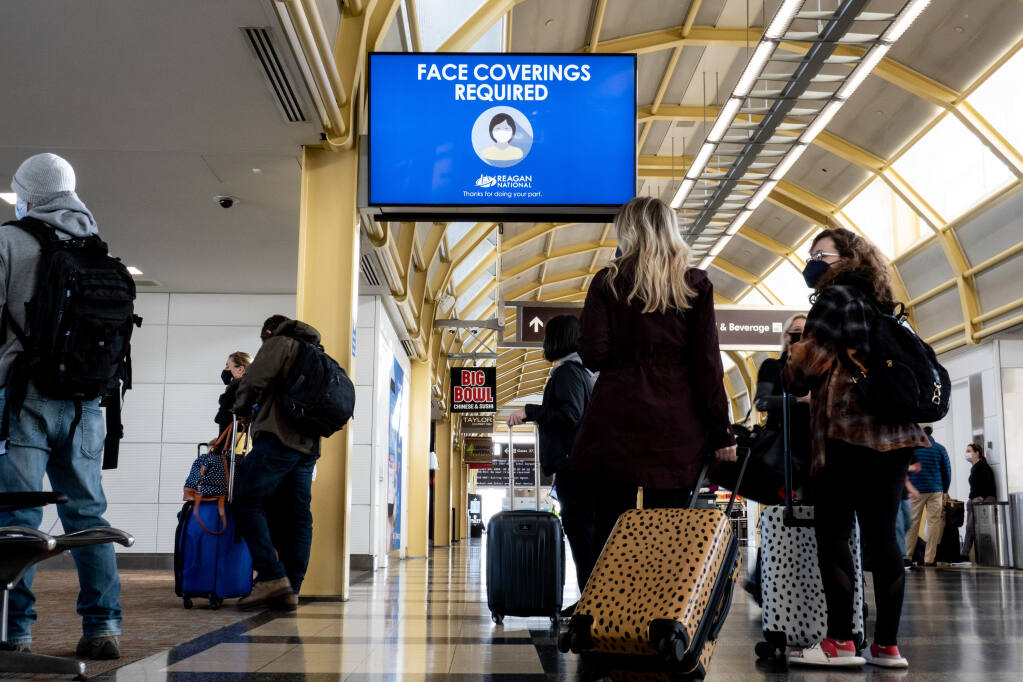 """Travelers pass through Ronald Reagan National Airport in Arlington, Virginia, near Washington, on Feb. 24, 2021. Businesses and universities want fast, easy ways to see if students and customers are vaccinated, but conservative politicians have turned """"vaccine passports"""" into a cultural flash point. (Erin Schaff/The New York Times)"""