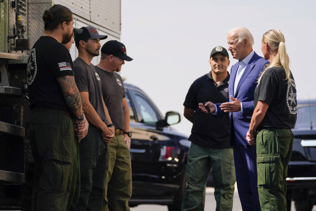 President Joe Biden greets firefighters as he tours the National Interagency Fire Center, Monday, Sept. 13, 2021, in Boise, Idaho. (AP Photo/Evan Vucci)
