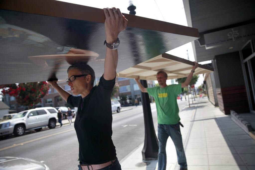 Vintner's Collective owner Kim Erasmy and employee Erick Smith, remove artwork from the damaged Pfeiffer Building following Sunday's earthquake on Monday, August 25, 2014 in Napa, California. (BETH SCHLANKER/ The Press Democrat)