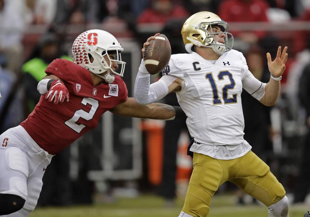 Stanford's Curtis Robinson, left, pressures Notre Dame quarterback Ian Book in the first half Saturday, Nov. 30, 2019, in Stanford. (AP Photo/Ben Margot)