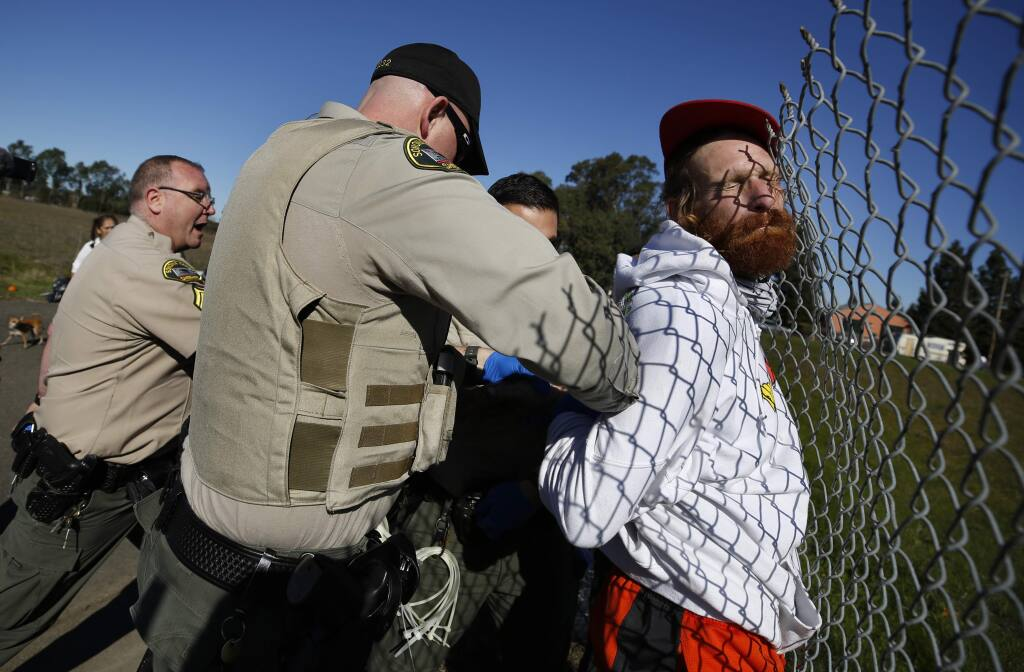 Sonoma County sheriff's deputies restrain a homeless man after an altercation at a homeless encampment along an unused portion of Bane Avenue just south of West Robles Avenue in Santa Rosa on Monday, Feb. 10, 2020. (BETH SCHLANKER/ PD)