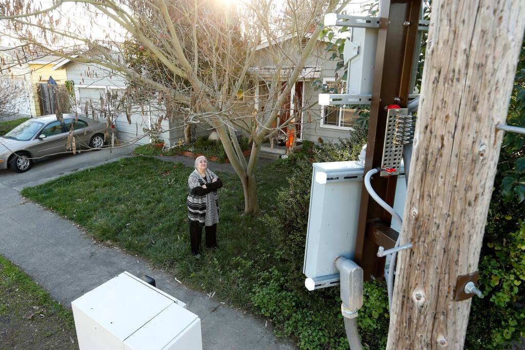 Judith Monroy poses for a portrait in her front yard, looking up at a Verizon Wireless cell signal booster, on a utility pole at right, and its in-ground utility box, lower left, that were installed in front of her home on Link Lane in Santa Rosa, California, on Friday, January 12, 2018. Neighborhood residents are upset at Verizon Wireless because only one resident, Monroy's next door neighbor, was notified in writing prior to the installation, as well as the size and proximity of the transmitters to their homes. (Alvin Jornada / The Press Democrat)
