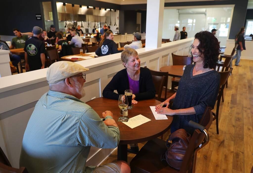 Russian River Brewing Company co-owner Natalie Cilurzo, right, visits with Wendy Petersen and Gerald King at the new Russian River Brewing Company location in Windsor on Tuesday, October 9, 2018. (Christopher Chung/ The Press Democrat)