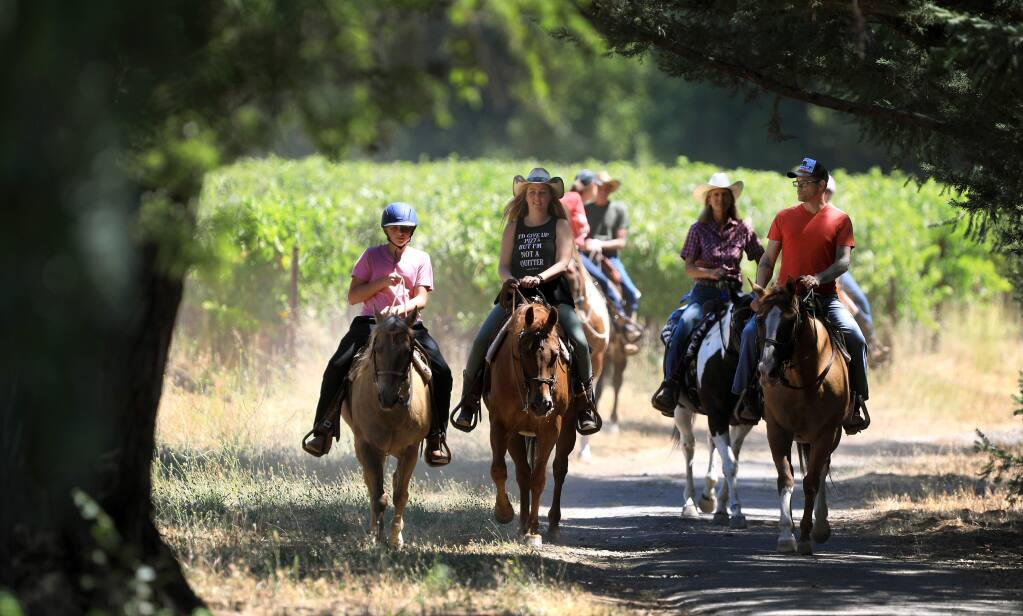 Aiden, 12, Erica and Josh Hartwig, of Florida, finish a trail ride led by Michelle Rogers of Sonoma Valley Trail through vineyards around Bartholomew Estate Winery in Sonoma, Friday, Aug. 2, 2019. (Kent Porter / The Press Democrat) 2019