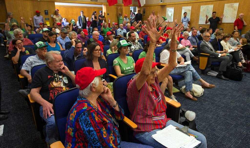 Supporters of marijuana farmers, wearing green, and opponents of marijuana grows in their neighborhoods, in red, filled the Sonoma County Supervisors chambers and the hallway outside for a meeting on changes to cannabis policies. (photo by John Burgess/The Press Democrat)