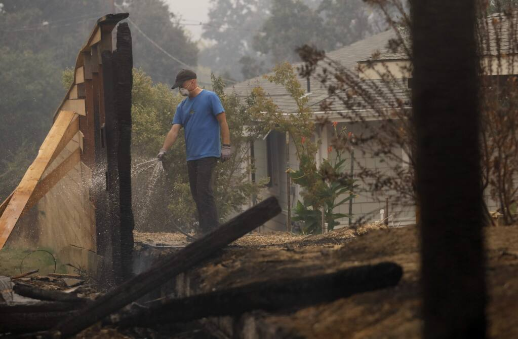 Jim Sillars puts out a fire that burned the fence on his friend's property on Monday, October 9, 2017 in Glen Ellen, California . (BETH SCHLANKER/The Press Democrat)