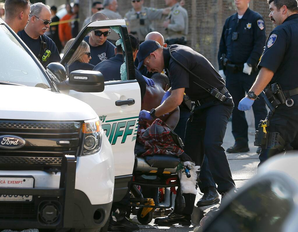 Medical personnel and law enforcement officers tend to a man on a gurney after an officer-involved shooting near the intersection of 9th and Morgan streets in Santa Rosa, California, on Thursday, Aug. 1, 2019. (ALVIN JORNADA/ PD)