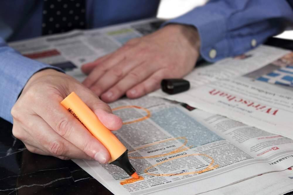 A job seeker marks jobs he's interested in in a newspaper's classified section. (Stock photo)