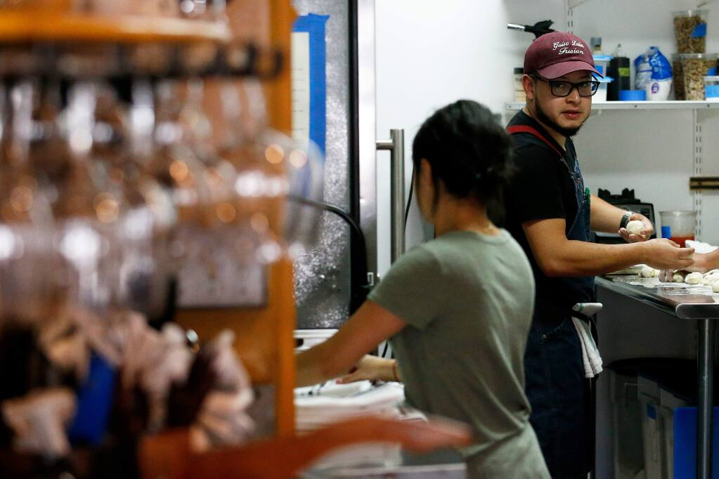 Carlos Mojica, right, chef and owner of Guiso Latin Fusion, chats with his sister Valeria Mojica, who also works at the restaurant as a server, as they prepare for a 2019 dinner service at his restaurant in Healdsburg, California. The restaurant was one of 50 hospitality businesses that banded together to sue Gov. Newsom over pandemic restrictions. Now that outdoor dining is allowed, the lawsuit has been dropped.  (Alvin A.H. Jornada / The Press Democrat)