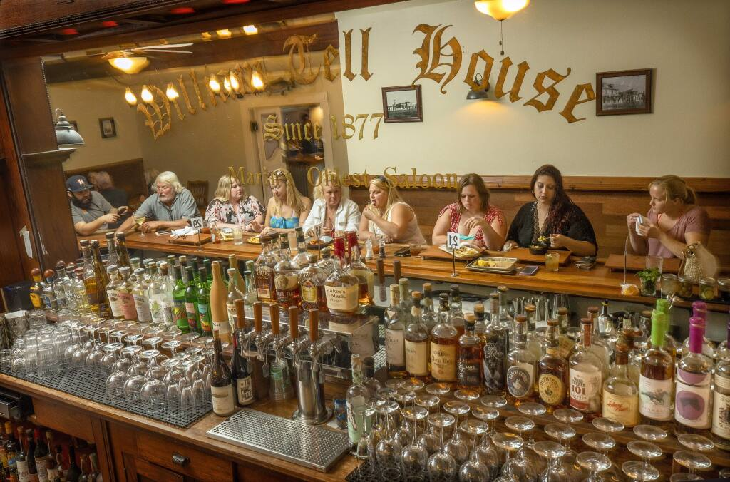 Local friends enjoy a drink and appetizers at the bar at the William Tell House in Tomales. (John Burgess/The Press Democrat)