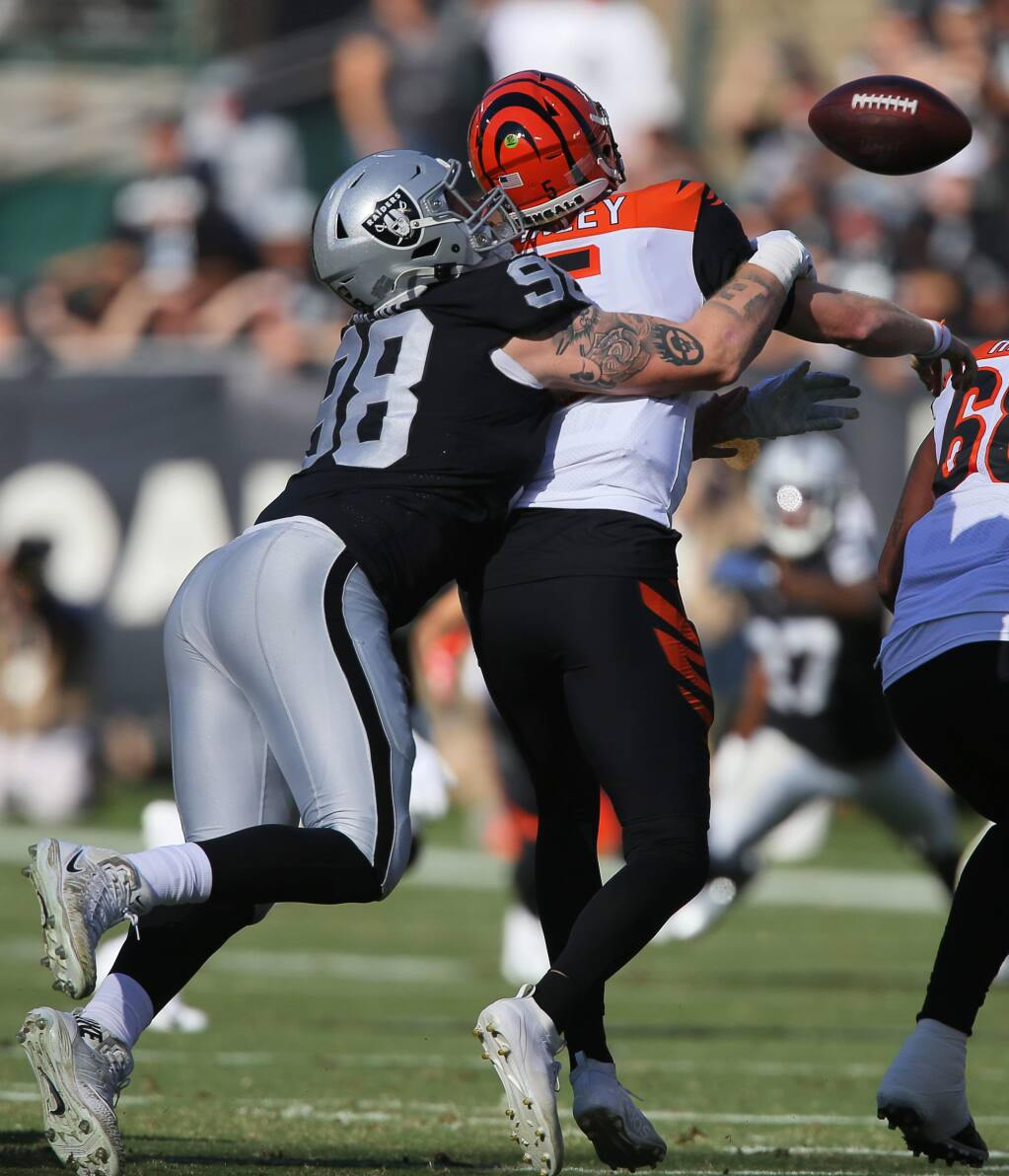 Oakland Raiders defensive end Maxx Crosby strips the ball from Cincinnati Bengals quarterback Ryan Finley during their game in Oakland on Sunday, November 17, 2019. (Christopher Chung/ The Press Democrat)