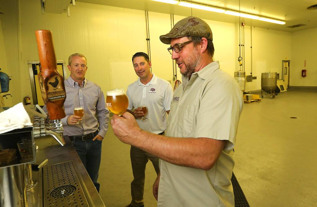 JOHN BURGESS / The Press Democrat) HenHouse Brewing Co. co-owner Scott Goyne, right, pours a beer for Live Oak Bank senior lenders Randall Behrens, center, and Tracy Sheppard at the company's new production facility in Santa Rosa.