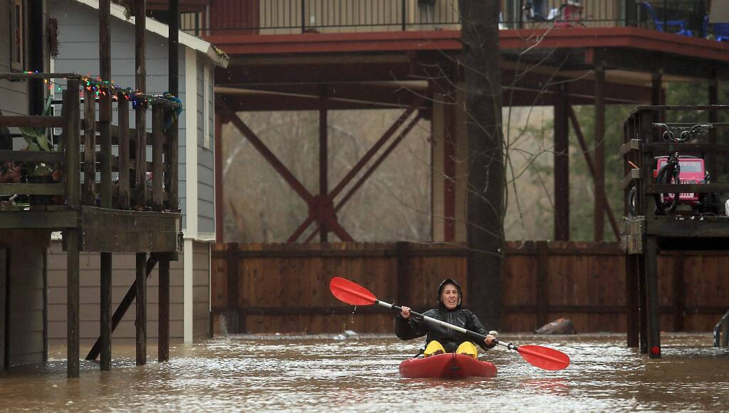 Elizabeth Hamilton, a resident of Sycamore Court Apartments, kayaks around the complex looking to see if anyone needed a lift out of the flood waters in Guerneville, Tuesday Jan. 10, 2017. (Kent Porter / The Press Democrat) 2017