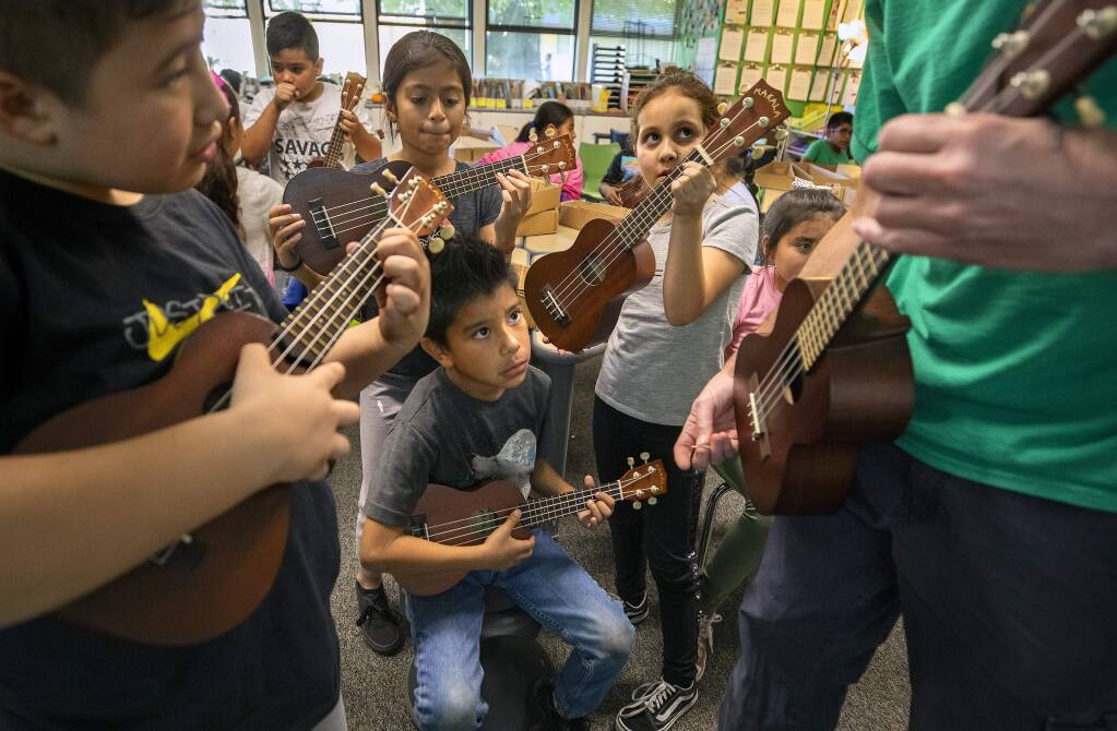 Clockwise from left, third graders Danny Avalos, Fatima Arevalo, Yuliana Miranda and Anthony Ayala-Sanchez learn the fingering for the 'Evil G-note' on the ukulele from teacher Steve Ciaffa at Roseland elementary school. (photo by John Burgess/The Press Democrat)