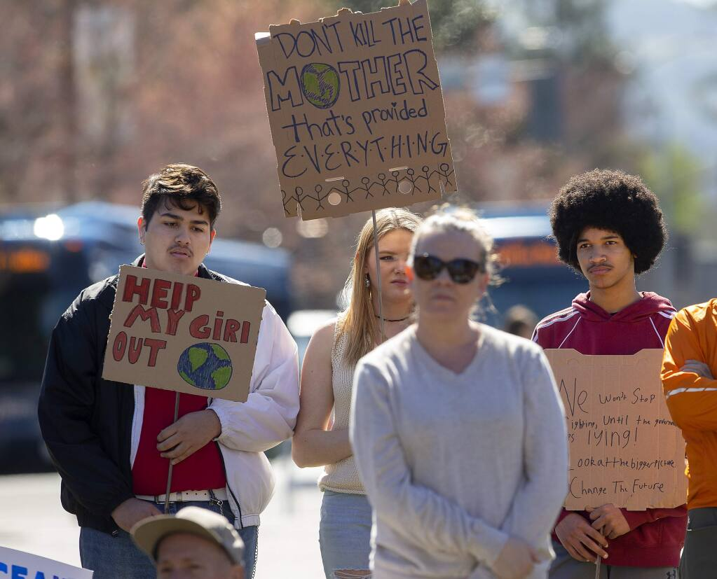 Students painted signs and their arms to demand action against climate change during a rally in Courthouse Square in Santa Rosa on Friday. The rally was a coordinated event with students around the U.S. and the world. (photo by John Burgess/The Press Democrat)
