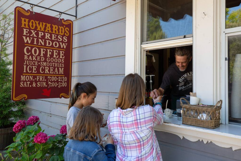Barista Derek Voges helps kids with their ice cream orders at the Howard's Station Cafe Express Window, in Occidental, California, on Wednesday, July 24, 2019. (Alvin Jornada / The Press Democrat)