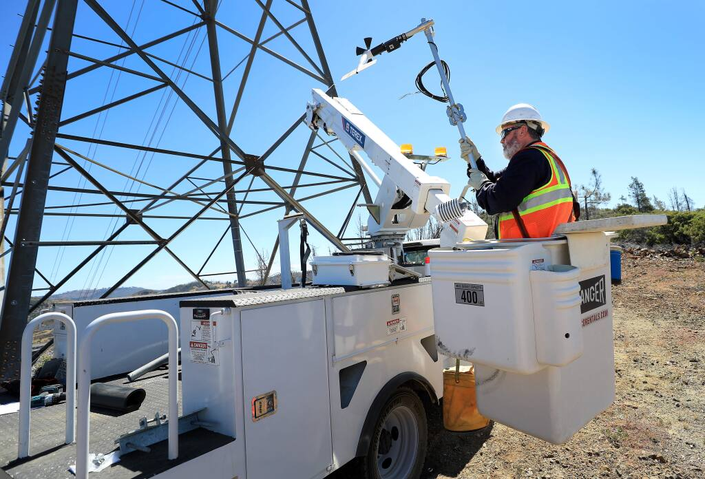 Pacific Gas and Electric communication technicians Mike Fortin prepares to install a wireless solar-powered weather monitoring station on a transmission tower above Pine Flat Road in the Mayacamas Mountains of eastern Sonoma County on Tuesday, July 23, 2019. (KENT PORTER/ PD)